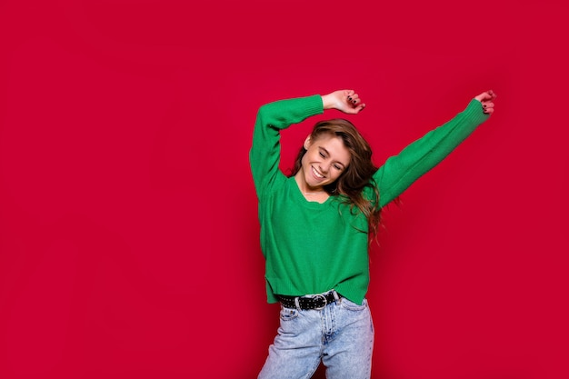 Elegante ragazza hippie su rosso che tira su le mani, celebra il nuovo anno, indossa un maglione verde e jeans, felice festa in discoteca di carnevale, coriandoli scintillanti, tiene il bicchiere, divertendosi Foto Gratuite