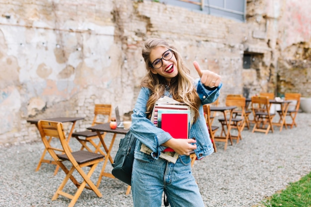 Stylish hipster girl in the retro jeans suit posing in front of the old brick wall. trendy young woman with bag standing next to old building. Free Photo
