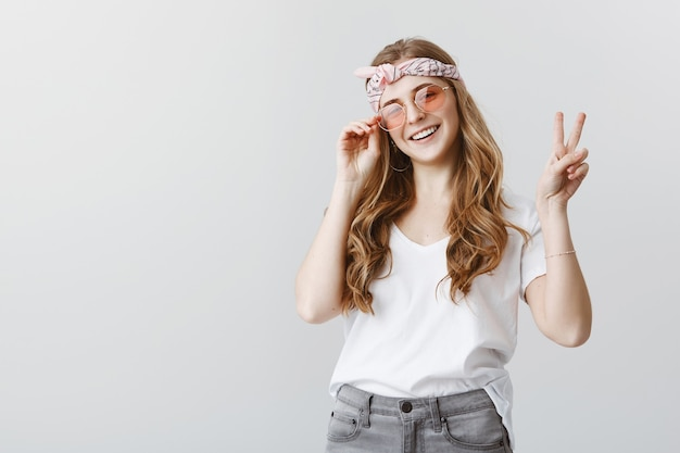 Ragazza alla moda hipster in occhiali da sole sorridendo felice, mostrando il segno di pace Foto Gratuite