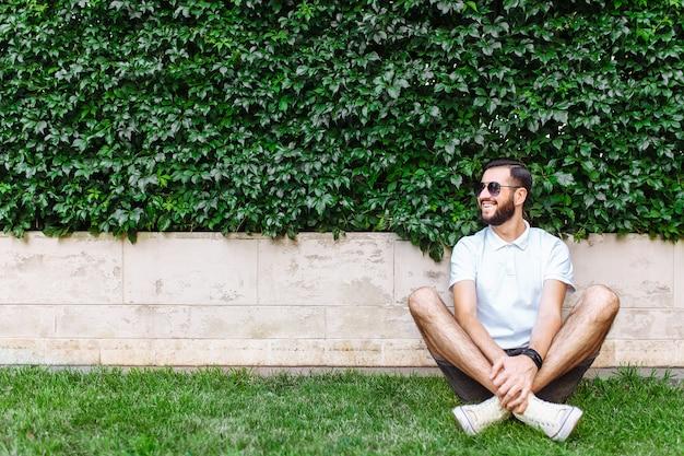 ひげと白いtシャツを着たスタイリッシュなヒップスター。落葉性の緑の壁にある芝生の上に座っています。 Premium写真