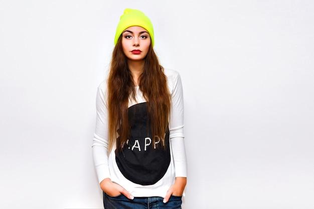 Стильная хипстерская женщина позирует на фоне белой стены, зимнее время, свитер, неоновая шляпа и джинсы, повседневная модная спортивная одежда, длинные волосы, яркий макияж, вспышка, серьезное сексуальное лицо. Бесплатные Фотографии