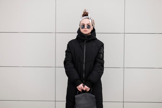 흰 벽 근처 가죽 세련 된 배낭과 세련 된 긴 재킷에 두건에 세련 된 선글라스에 세련 된 Hipster 젊은 여자. 미국의 현대 소녀. 여성 패션. 프리미엄 사진