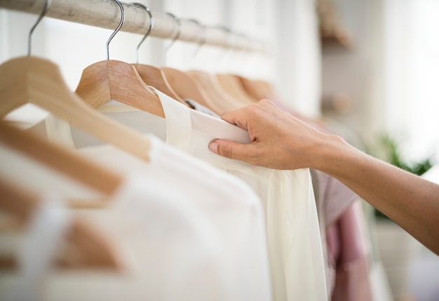 A stylish is choosing cloth from the rack Premium Photo