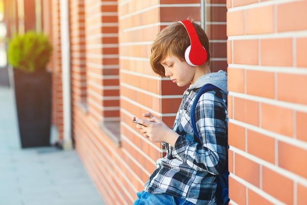 Stylish kid boy with headphones using phone at city street. young boy plays online game at smartphone. preteen boy listens to the music on smart phone Premium Photo