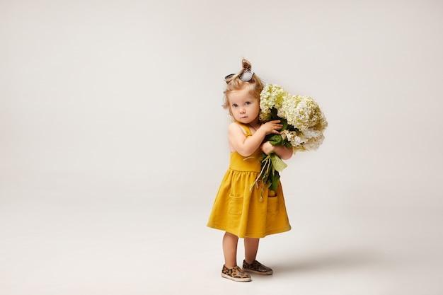 흰색 배경에 고립 된 야생 꽃의 꽃다발을 들고 노란 드레스에 세련 된 소녀. 아동 패션. 공간 복사 프리미엄 사진