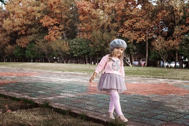 Stylish little girl walking in autumnal park Premium Photo