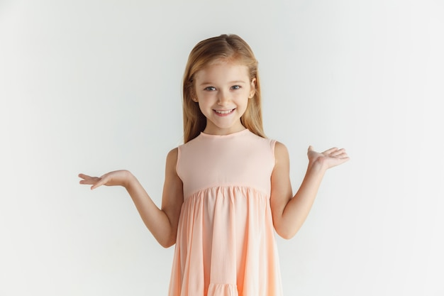Stylish little smiling girl posing in dress isolated on white wall. caucasian blonde female model. human emotions, facial expression, childhood. smiling, astonished, wondered. Free Photo