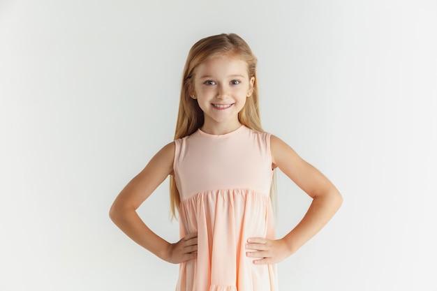 白い壁に隔離のドレスでポーズをとってスタイリッシュな小さな笑顔の女の子。白人の金髪女性モデル。人間の感情、表情、子供時代。笑顔で、ベルトに手をつないで。 無料写真