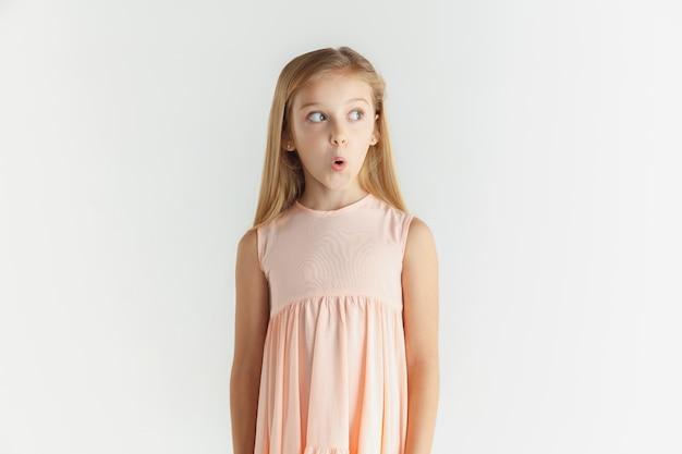 Стильная маленькая улыбающаяся девочка позирует в платье, изолированном на белой стене. кавказская женская модель. человеческие эмоции, мимика, детство. удивился, удивился, потрясен. глядя в сторону. Бесплатные Фотографии