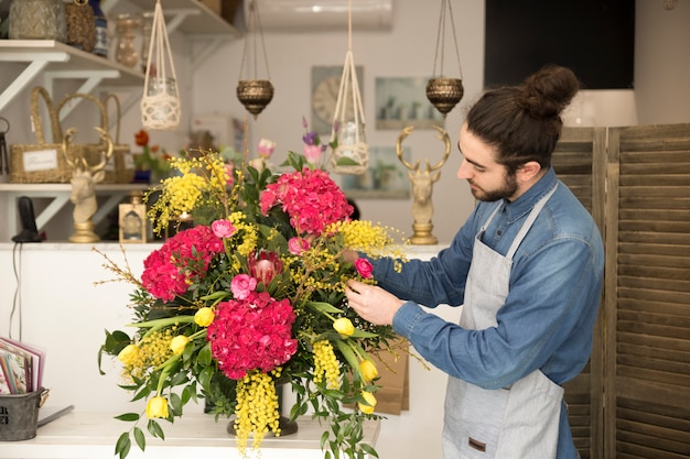 Stylish male florist create flower bouquet on table in the shop Free Photo