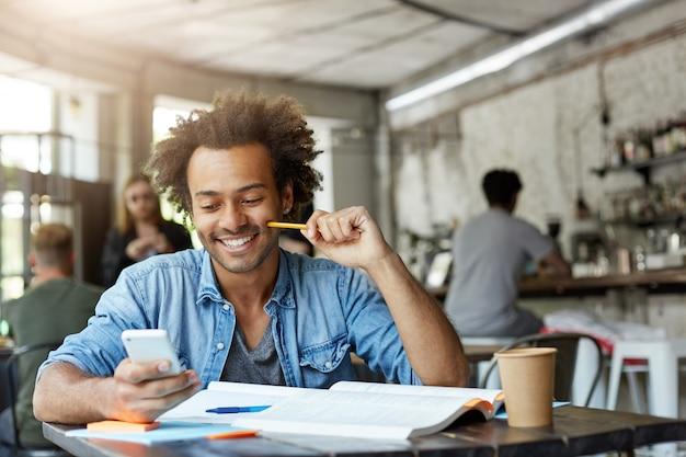 Стильный студент мужского пола, работающий в кафетерии Бесплатные Фотографии