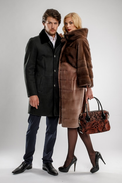 Stylish man and glamour woman in fur coat posing with winter outfit. Premium Photo