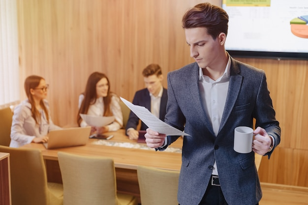 A stylish man in a jacket and a shirt with a cup of coffee in his hand stands and reads documents on the background of working colleagues at office Premium Photo