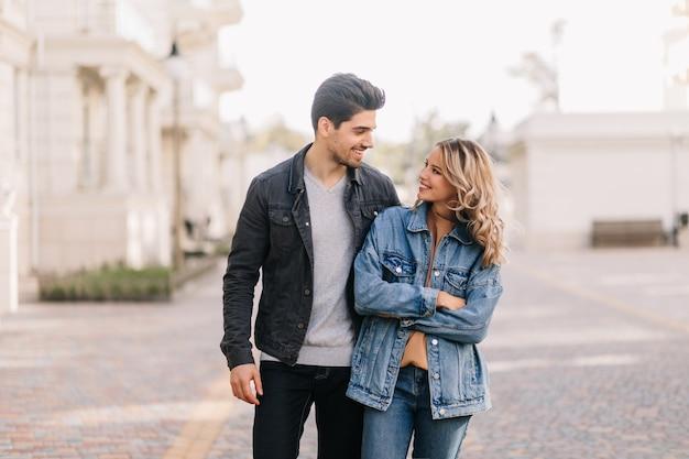 愛を込めてガールフレンドを見ているスタイリッシュな男。デートで楽しんでいる巻き毛の女の子の屋外の肖像画。 無料写真