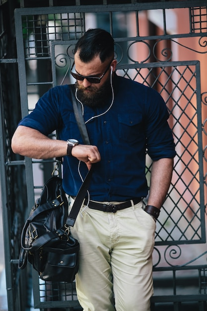 Stylish man looking at his wristwatch Free Photo