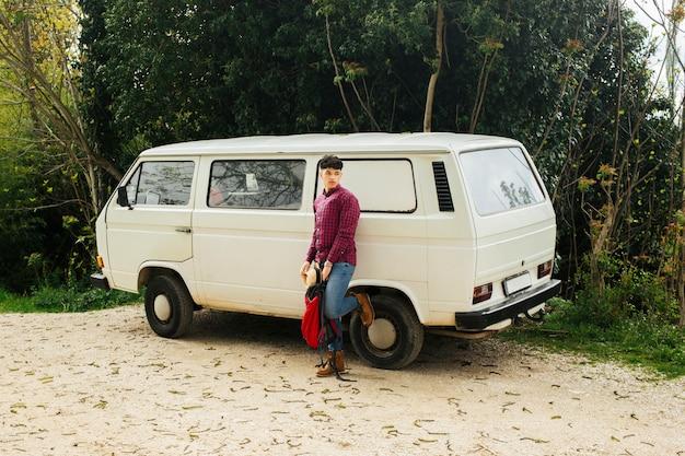 Stylish man posing near white van with holding backpack Free Photo