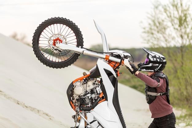 砂漠でバイクを上げるスタイリッシュな男 無料写真