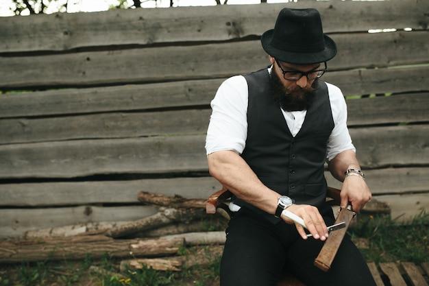 Stylish man sharpening a razor Free Photo