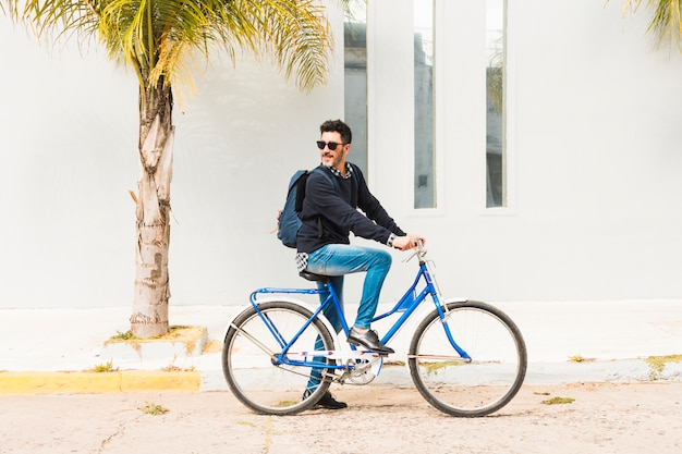 Stylish man with his backpack riding on blue bicycle Free Photo