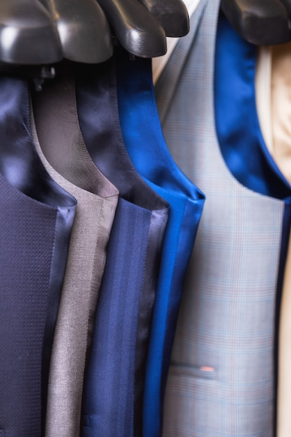 Stylish men's vest close up. male svest hanging in a row. Premium Photo