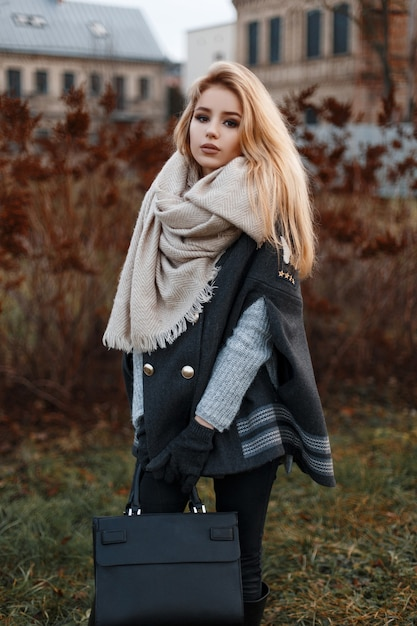 가죽 패션 가방이 달린 검은 청바지에 스카프가 달린 검은 코트에 회색 니트 스웨터에 세련된 현대 젊은 여성이 도시의 마른 잔디 근처에 서 있습니다. 매력적인 소녀. 프리미엄 사진