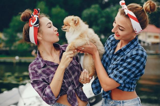 Stylish pin up girls with the little dog Free Photo