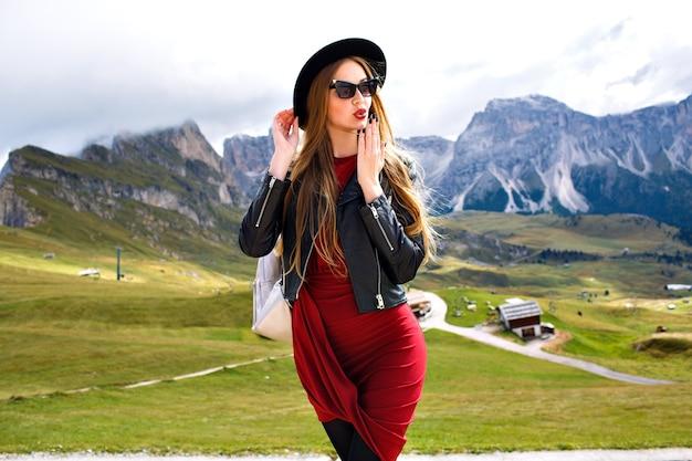 イタリアのドロミテ山脈でポーズをとって、エレガントな女性のスタイリッシュな肖像画 無料写真