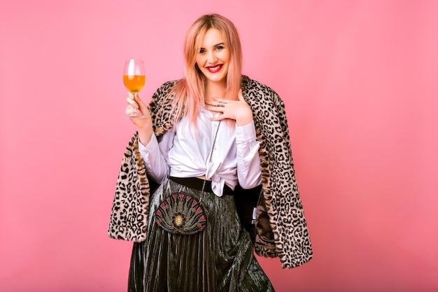 スタイリッシュな肯定的なかなり若い女性が楽しんで、夜の輝くカクテルの服と毛皮のヒョウ柄の流行のコート、ピンクの背景を着て、冬の休日のパーティーを楽しんでいます。 無料写真