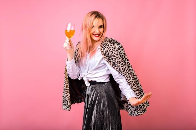 Стильная позитивная симпатичная молодая женщина веселится, одетая в вечерний сверкающий коктейльный наряд и модное пальто с меховым леопардовым принтом, розовый фон, наслаждаясь вечеринкой зимних праздников. Бесплатные Фотографии