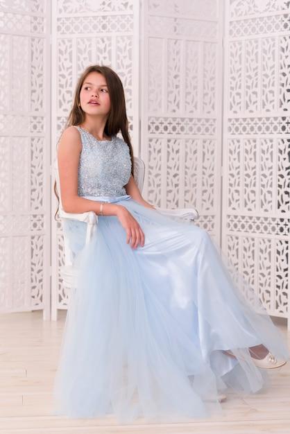 Ragazza graziosa alla moda che si siede sulla sedia a casa Foto Gratuite