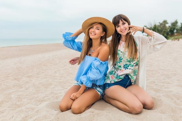 Eleganti belle donne sedute sulla sabbia durante le vacanze estive sulla spiaggia tropicale, stile bohémien, amici che viaggiano insieme, accessori di tendenza alla moda, emozione felice sorridente, umore positivo, cappello di paglia Foto Gratuite