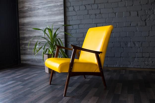 Stylish retro yellow chair in the gray room, brick gray wall, Premium Photo
