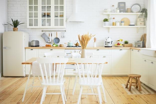 スタイリッシュなスカンジナビアのキッチンインテリア:前景の椅子とテーブル、冷蔵庫、機械付きの長い木製カウンター、棚の上の調理器具。インテリア、デザイン、アイデア、家と居心地のよさのコンセプト 無料写真