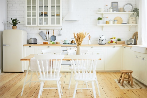Stylish scandinavian kitchen interior: chairs and table in foreground, fridge, long wooden counter with machines, utensils on shelves. interiors, design, ideas, home and coziness concept Free Photo
