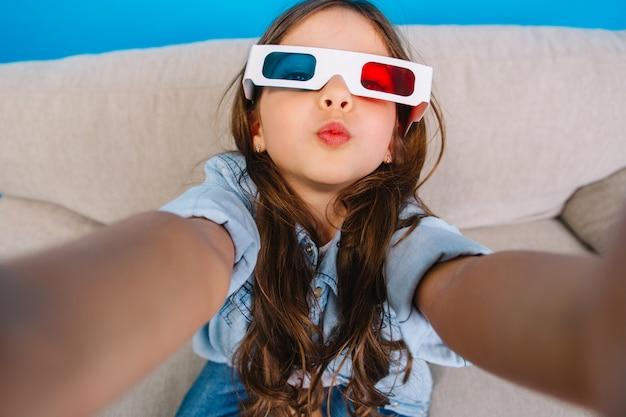Стильный автопортрет очаровательной маленькой девочки в 3d-очках, отправляющей поцелуй в камеру. отдыхая на диване на синем фоне, в джинсовой одежде, с длинными волосами брюнетки, выражая счастье Бесплатные Фотографии