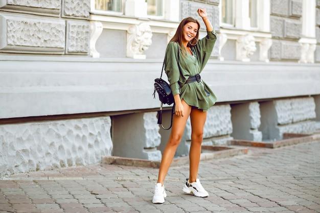 Стильная сексуальная веселая великолепная девушка-модель позирует на улице Бесплатные Фотографии