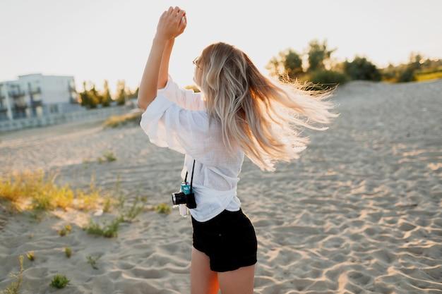 Elegante ragazza formosa con retro macchina fotografica in posa sulla soleggiata spiaggia serale. vacanze estive. umore tropicale. libertà e concetto di viaggio. Foto Gratuite