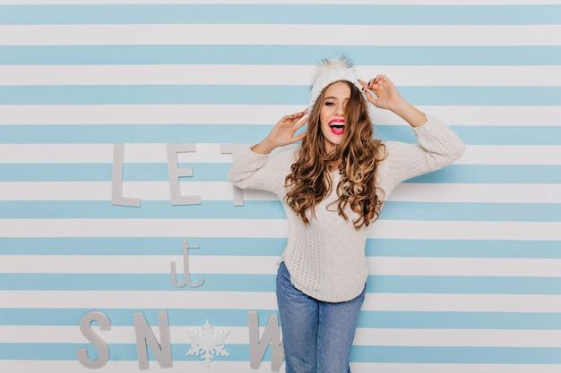 黒髪が笑って楽しくポーズをとるスタイリッシュでスリムなモデル。美しいテキストで壁に白い服を着た女の子の肖像画 無料写真