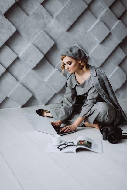 Стильная умная привлекательная элегантная красивая блондинка деловая женщина в сером строгом костюме и берете смотрит на ноутбук в сером кабинете в стиле лофт. Premium Фотографии