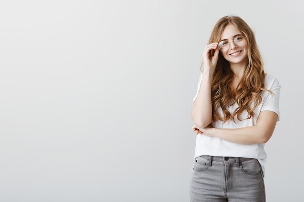 Studentessa bionda sorridente alla moda in vetri che sembrano felici Foto Gratuite