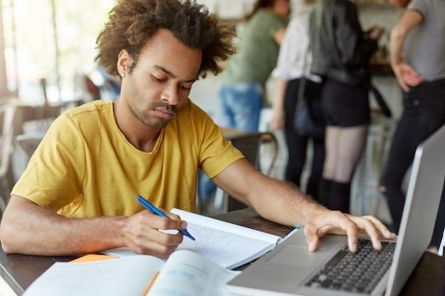 Maschio elegante studente seduto nel ristorante alla scrivania in legno scrivendo qualcosa nel suo quaderno digitando sulla tastiera del suo laptop guardando seriamente verso il basso. preparazione per esami o lezioni Foto Gratuite