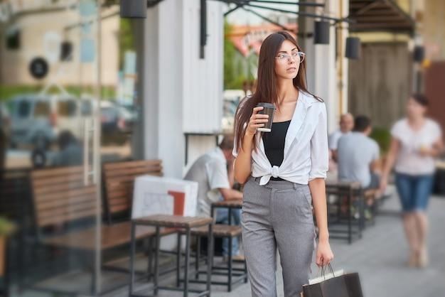 Stylish student walking in downtown drinking coffee. Premium Photo