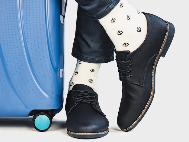 Stylish suitcase, men's legs and bright socks Premium Photo