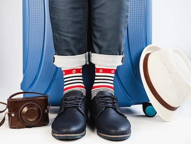 Stylish suitcase, men's legs and multicolored socks Premium Photo
