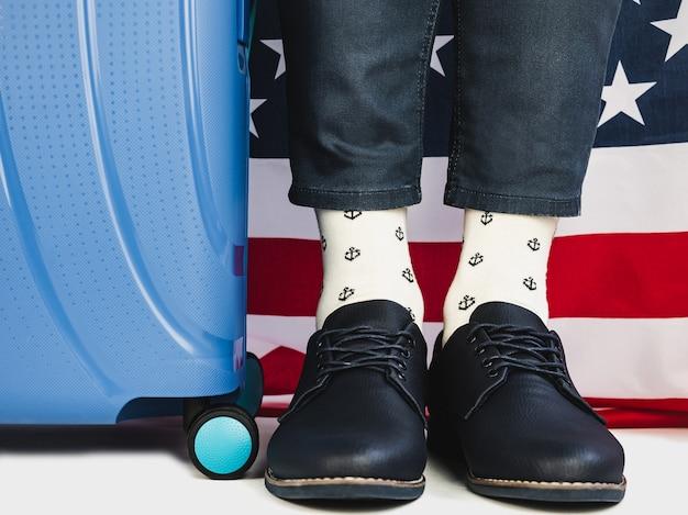 Stylish suitcase, us flag and men's legs Premium Photo