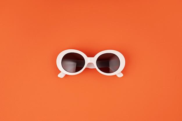 オレンジ色の壁にスタイリッシュなサングラス。夏のファッション、パーティー、夏のスタイル、休暇のコンセプト。最小限のフラットレイ、上面図 Premium写真