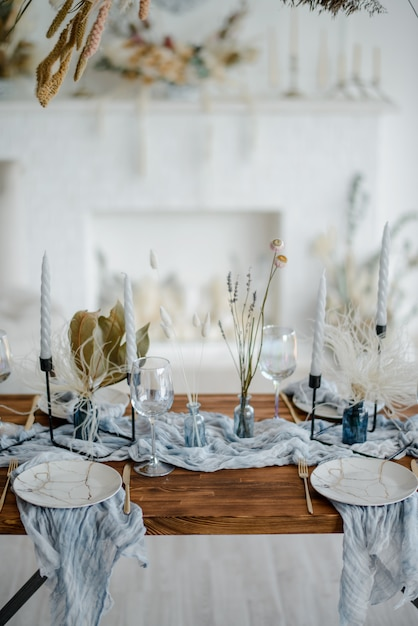 Premium Photo Stylish Table Setting With Dried Flowers Plate With Vintage Golden Fork And Knife Candles Dusty Blue Napkins On Wooden Table Winter Wedding Decoration