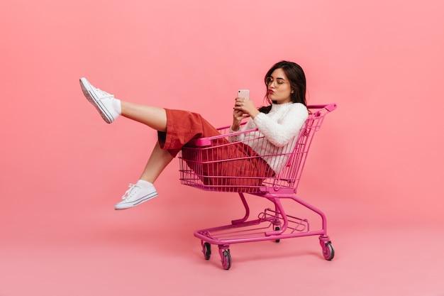 Стильная девочка-подросток в брюках и белом свитере сидит в тележке супермаркета. модель в очках посылает поцелуй и делает селфи на розовом. Бесплатные Фотографии