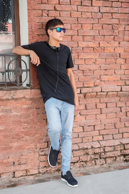Stylish teenage boy leaning on brick wall and listening music Free Photo