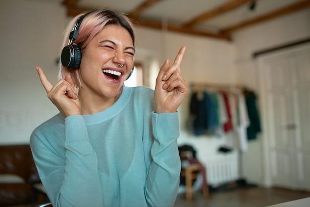 Elegante ragazza adolescente con i capelli rosa e piercing al viso divertirsi al chiuso, essere a casa da sola, ascoltare musica in cuffie wireless, chiudere gli occhi, fare mosse di danza, cantare insieme Foto Gratuite